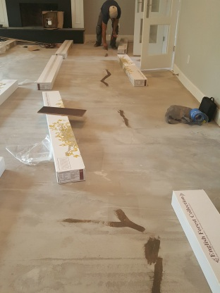 Sealing up cracks before installing wood flooring.